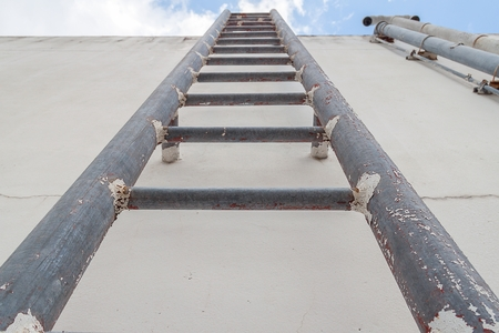 fall arrest: Old vertical industrial metal rusted ladder. Staircase to blue sky with clouds  no safety rails. Stock Photo