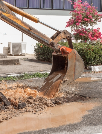 Excavator working on the Repair of  pipe water and sewerage on road, Worker using a small excavator to dig a hole to fix a water. (select focus  on excavator and soft-focus water)