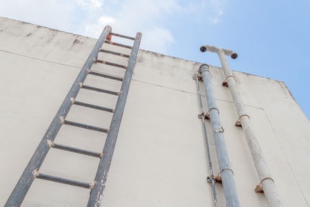 Old Vertical Industrial Metal Rusted Ladder. Staircase To Blue Sky With  Clouds No Safety Rails