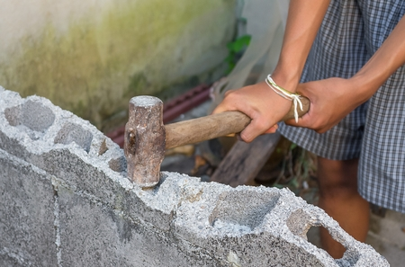 hammer in hand breaking brick wal  : young power use  Hammer smash a brick wall In construction : select focus Hammer, Blur blurred background. Stock Photo