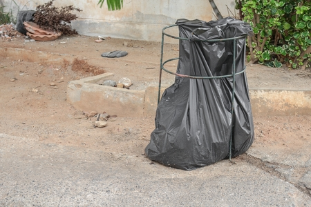 black plastic garbage bag: Black garbage bag.  Trash bag ,black plastic garbage bags front of house.
