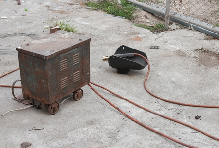 aegis: Old rust Welding equipment, welding mask, Old  still life of rod-holder with cable and electrode, for electric arc welding, on a cement floor. Select focus Welding rust.
