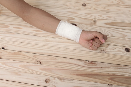 treating: Gauze bandage the  hand contusion. treating patients with hand with a wrist left, male With gauze is wrapping his injury On a wooden table .( select focus front Gauze bandage wrist and soft background) Stock Photo