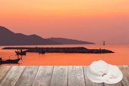 gloaming: White hat Two overlapping on a wooden floor. sunrise at sea Morning in nature : space for text  and may be used as background : Stock Photo