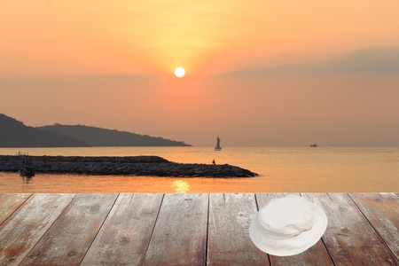 White hat on a wooden floor. sunrise at sea Morning in nature : space for text  and may be used as background : Stock Photo