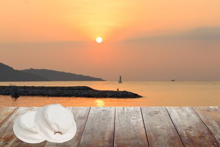 White hat Two overlapping on a wooden floor. sunrise at sea Morning in nature : space for text  and may be used as background : Stock Photo