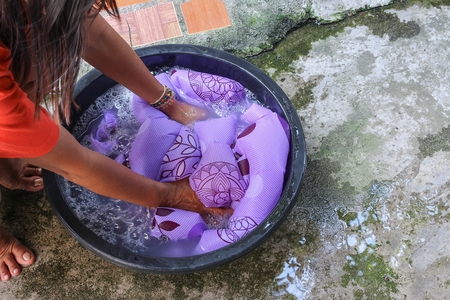 Woman wash hands dirty clothes in the basin black for cleansing,Thailand washing clothes style ancient and soak with detergent in the evening.