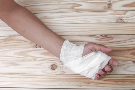 treating: Gauze bandage the hand contusion. treating patients with hand with a wrist left, male With gauze wrapping his injury On a wooden table .( select focus front Gauze bandage wrist and soft background) Stock Photo