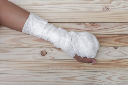 contusion: Gauze bandage the hand contusion. treating patients with hand with a wrist left, male With gauze wrapping his injury On a wooden table .( select focus front Gauze bandage wrist and soft background) Stock Photo