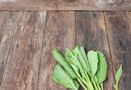 roughage: Chinese kale fresh vegetable on wooden table background, Top view with copy space. Stock Photo