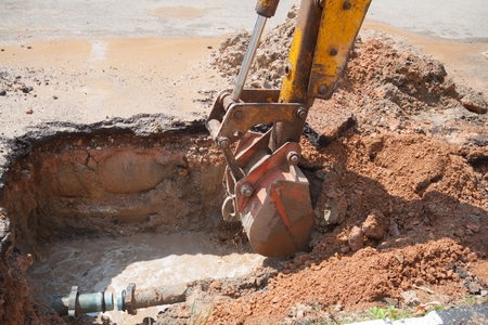 Excavator bucket selective focus, bulldozer work a hole the repair of pipe water and sewerage on road Imagens