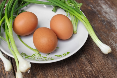fresh chicken egg on a plate Close up and onion in wooden table with copy space