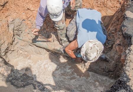 worker male repair plumbing broken  pipe in the hole with water flow