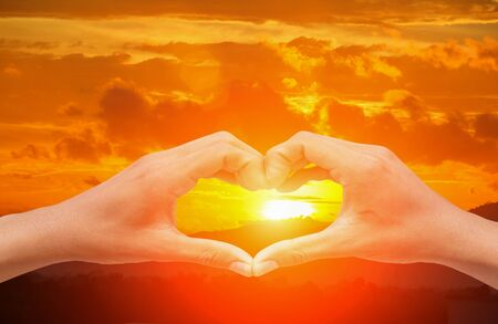 hand forming  a heart shape with  sunset  light and copy space for add text Stock Photo