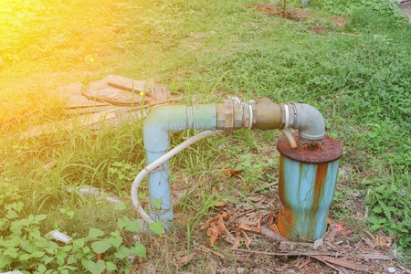 Water valve Plumbing pipe Steel dilapidated on grass. old rusty industrial tap with sunset light tone.