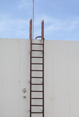fall arrest: Staircase old vertical industrial metal rusted. to Water tank no safety rails Stock Photo