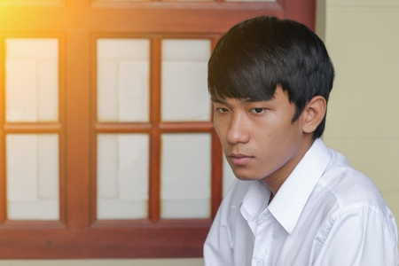 Young man handsome is sitting waiting in coffee shop with  light tone.