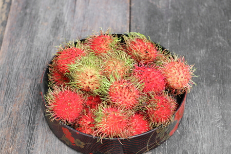 rambutan sweet fruit fresh in plate on wood background :Select focus with shallow depth of field. Stock Photo