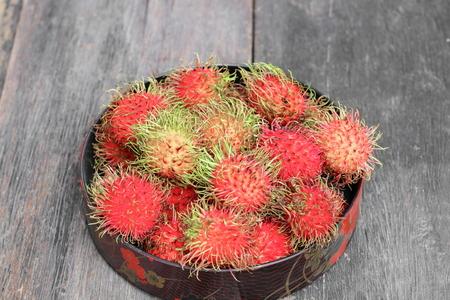 tiefe: rambutan sweet fruit fresh in plate on wood background :Select focus with shallow depth of field. Lizenzfreie Bilder