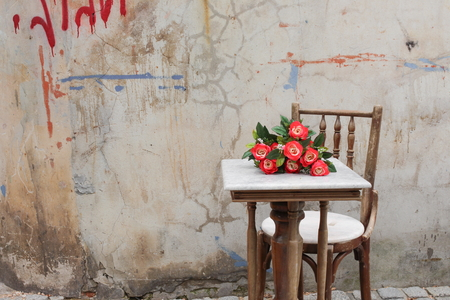 office furniture: flower red on table ancient at The background is the old wall