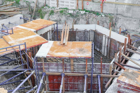 making hole: Hole of foundation construction building site making reinforcement metal framework for  pouring concrete Stock Photo