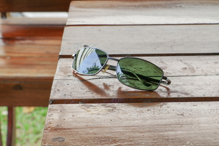 Black sunglasses on a wooden table. Stock Photo