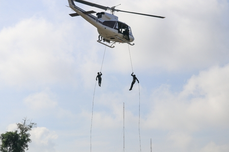 Soldier rappelling from helicopter in blue sky with blur propeller Stock Photo
