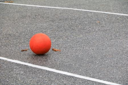 orange soccer ball on asphalt