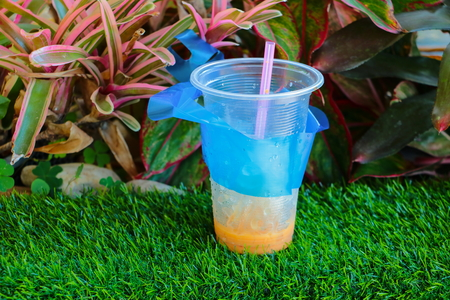 cold coffee in plastic cup on artificial grass green background with copy space add text