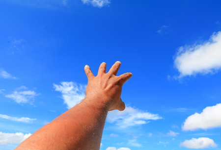 hand reach out so it the on  blue sky background 版權商用圖片