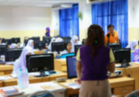 focus blur, the student with teacher learning business technology desktop computer in a classroom