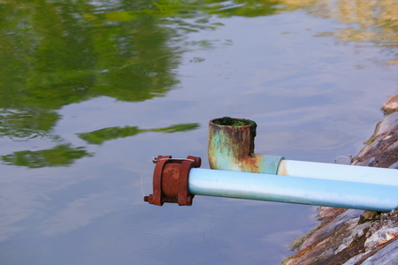sewage pipe pvc. polluting the river Stock Photo