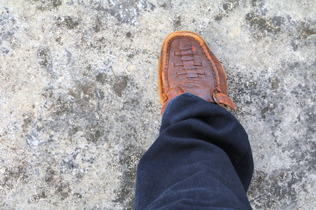 businessman leg right walking and brown leather shoe on the cement floor