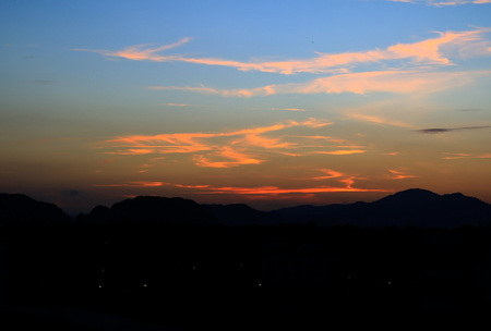 sunset in sky and cloud, beautiful colorful twilight time with mountain silhouette