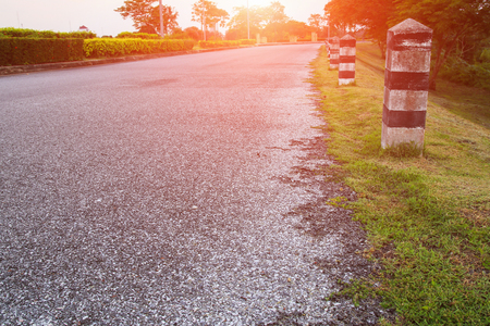 black and white painted milestone. in range roadside with sunset light tone Select focus with shallow depth of field.