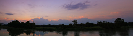 panorama sunset in sky beautiful colorful landscape silhouette tree woodland and river reflect the twilight time Stock Photo