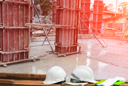Plastic safety helmet and blueprint on wood and worker construction team working building commercial in site workplace with sunrise light background Фото со стока
