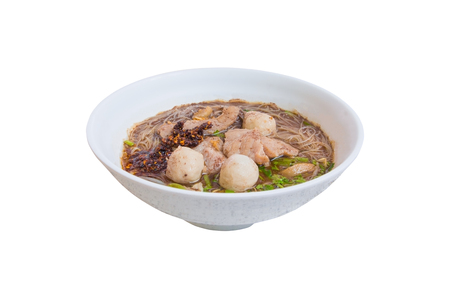 noodle meat ball and pig piece in bowl on table with broth intense. top view isolated oover  white background and clipping path