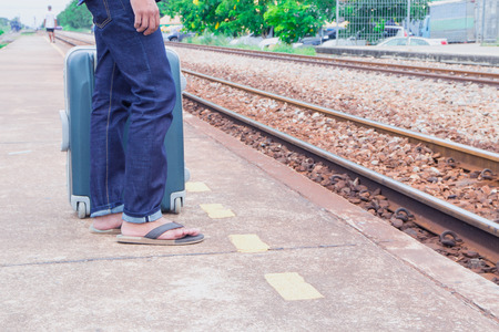 leg male of travel put jeans stand and suitcase wait train in station  trail platform with copy space