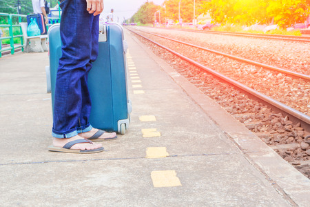 leg male of travel put jeans stand and suitcase wait train in station  trail platform with sunset light and copy space Stock Photo
