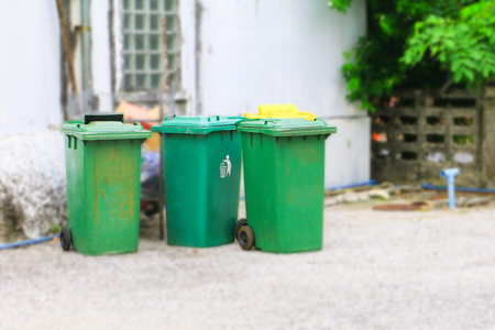 trashcan green rubbish bin dustbins outside and blurry wall background roadside in the city with copy space