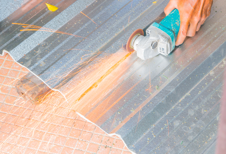 electric wheel grinding on cutting metal sheet roof  in constructor works. select focus with shallow depth of field