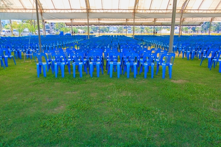 Row of blue chairs plastic on lawn in tent Imagens
