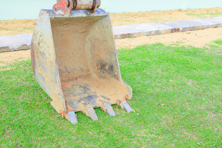 excavator bucket close up On the green grass Stock Photo