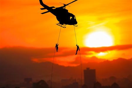 Silhouette Soldiers rappel down  to attack from helicopteron with sunset and copy space add text ( Concept stop hostilities To peace) Archivio Fotografico