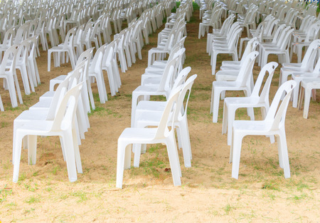 Row of white chairs plastic on lawn prepare business meeting