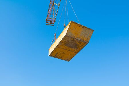 Tower crane bucket of yellow  in building construction site. blue sky background
