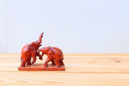 two wooden elephant conflict on wood floor table background with copy space add text