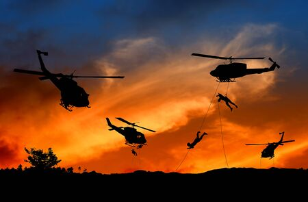 Silhouette Soldiers rappel down to attack from helicopter with sunset and copy space add text