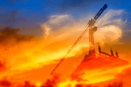 Silhouette Tower crane construction work on sunset time background and copy space add text concept double exposure